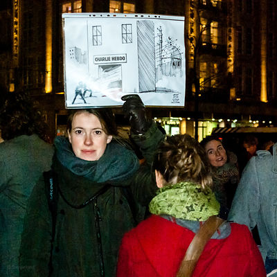 Amsterdam, Netherlands 2015-01-08: Demonstration and protest rally: 'Je suis Charlie' . Lady holding a cartoon.
