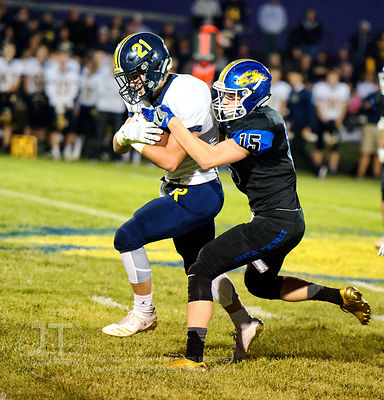 Wilton's Drake Hayes (15) tackles Iowa City Regina's Jacob Phillips (21) during the first half of play in Wilton on Friday, S...