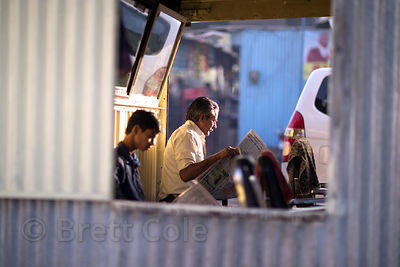Barbers read the newspaper at sunrise at the Marwar bus stand in Pushkar, Rajasthan, India