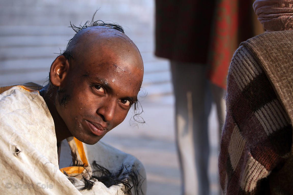 A Hindu man has his head shaved as part of a religious ritual, Assi Ghat, Varanasi, India.