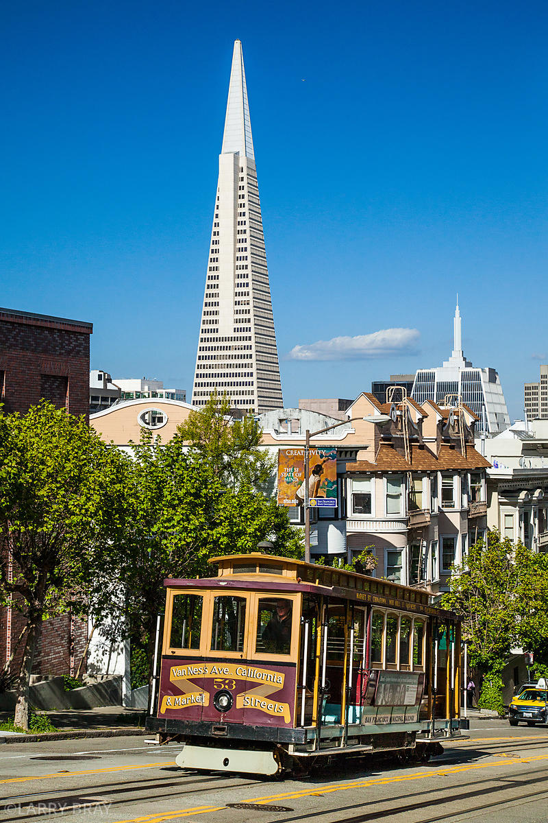 Cable car with the Transamerica Pyramid building in distance in San Francisco, California, USA