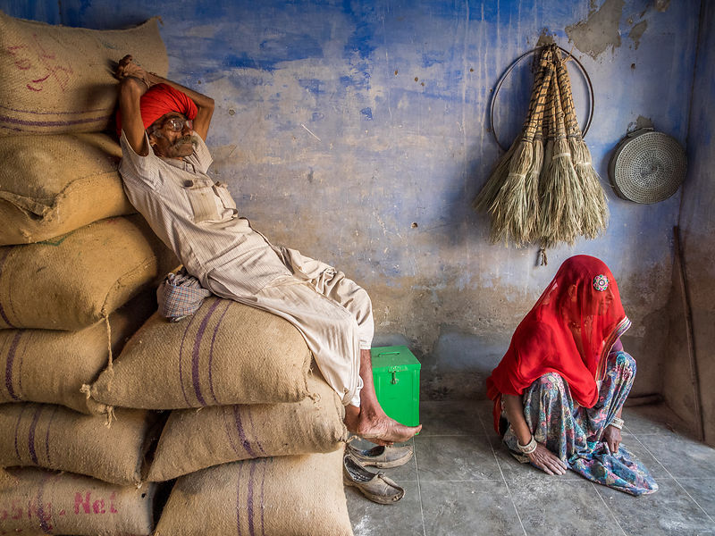 A rural man rests while the woman sits, attentively on the ground. This is a common scene at any Indian village. This photogr...