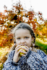 Younger Nordic girl eating a pear