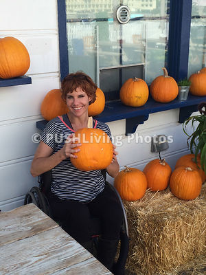 Woman in a wheelchair buying pumpkins for Halloween