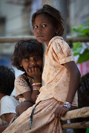 Two homeless sisters watch the procession of the Lalbaug Racha during the Ganesh Chaturthi festival in Mumbai, India
