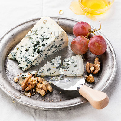 Dor Blue Cheese with honey, nuts and grapes on plate