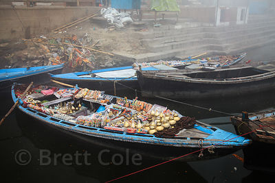 Boats loaded with tourists sourvernis on the Ganges River in Varanasi, India. Salesmen will pull up next to tourist boats on ...