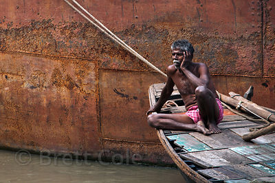 A fisherman relaxes in his boat on the Hooghyl River, Kolkata, India.