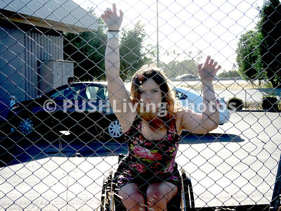 Young woman in a wheelchair against a chain mail security fence