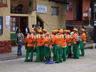 A gang of female street-sweepers in orange uniforms waiting for instruction, Aguas Calientes, Peru