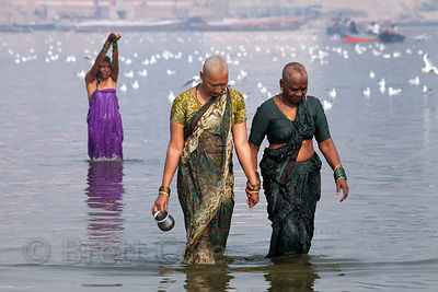 Two Hindu women shave their heads and bathe in the Ganges River as part of a religious ritual, Varanasi, India.