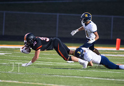 Iowa City Regina's Kieler Brown (3) tackles  Solon's Adam Bock (32) during the first half of play in Solon on Friday, Septemb...