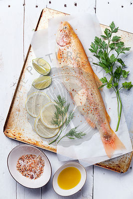 Raw fish golden trout with spices on wooden background