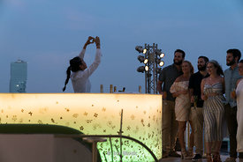 A waitress takes a picture of tourists at the Sky Bar in State Tower, Bangkok, Thailand.