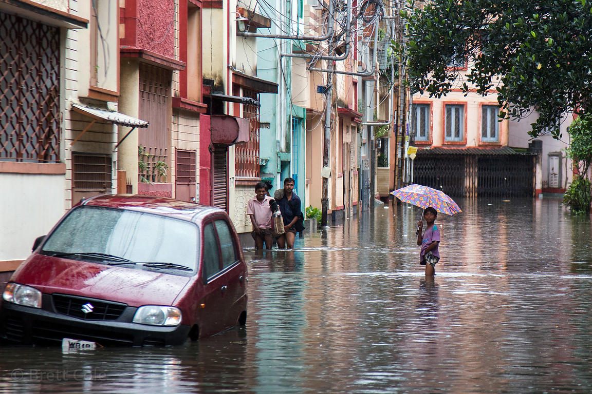 A girl walks though high water with an umbrella during monsoon flooding, Lake Gardens, Kolkata, India. Taken during the heavi...