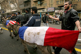 Donkeys draped in French, American, British and other western flags are led by Iranian protestors in front of the British em...