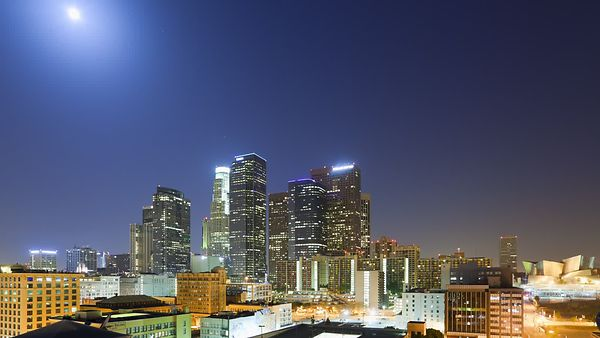 Wide Shot: Moon Orbits Twinkling High-Rises followed By A  Sun Rise