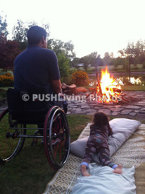 Man in a wheelchair with his daughter in front of their firepit