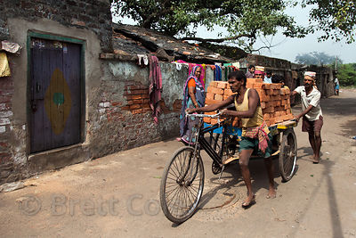 A worker hauls a cart full of bricks by bicycle in Howrah, India