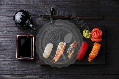 Nigiri Sushi set on wooden serving board and soy sauce on black wooden background