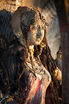 An idol that was immersed in the Hooghly River stands covered in dirt from the river, Sovabazar, Kolkata, India.