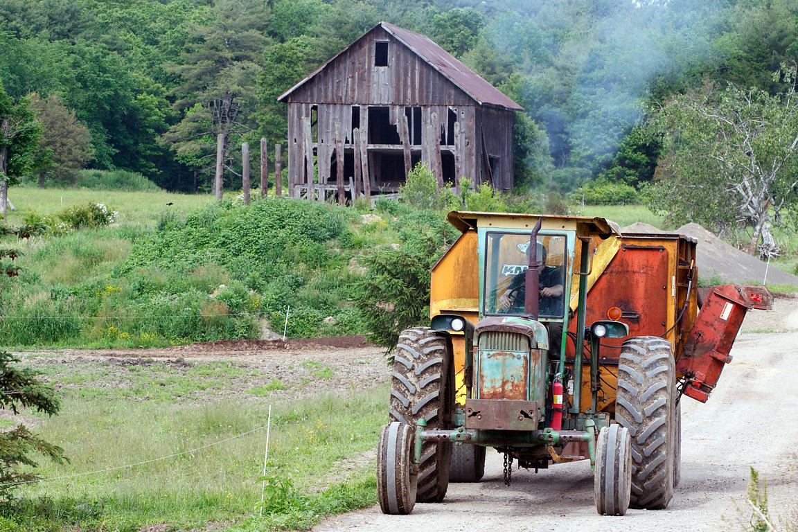 A tractor passes what is one of the oldest surviving barns in the United States, on a farm in Rochester, Shawangunks, New York