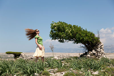 Woman with windblown hair and tree