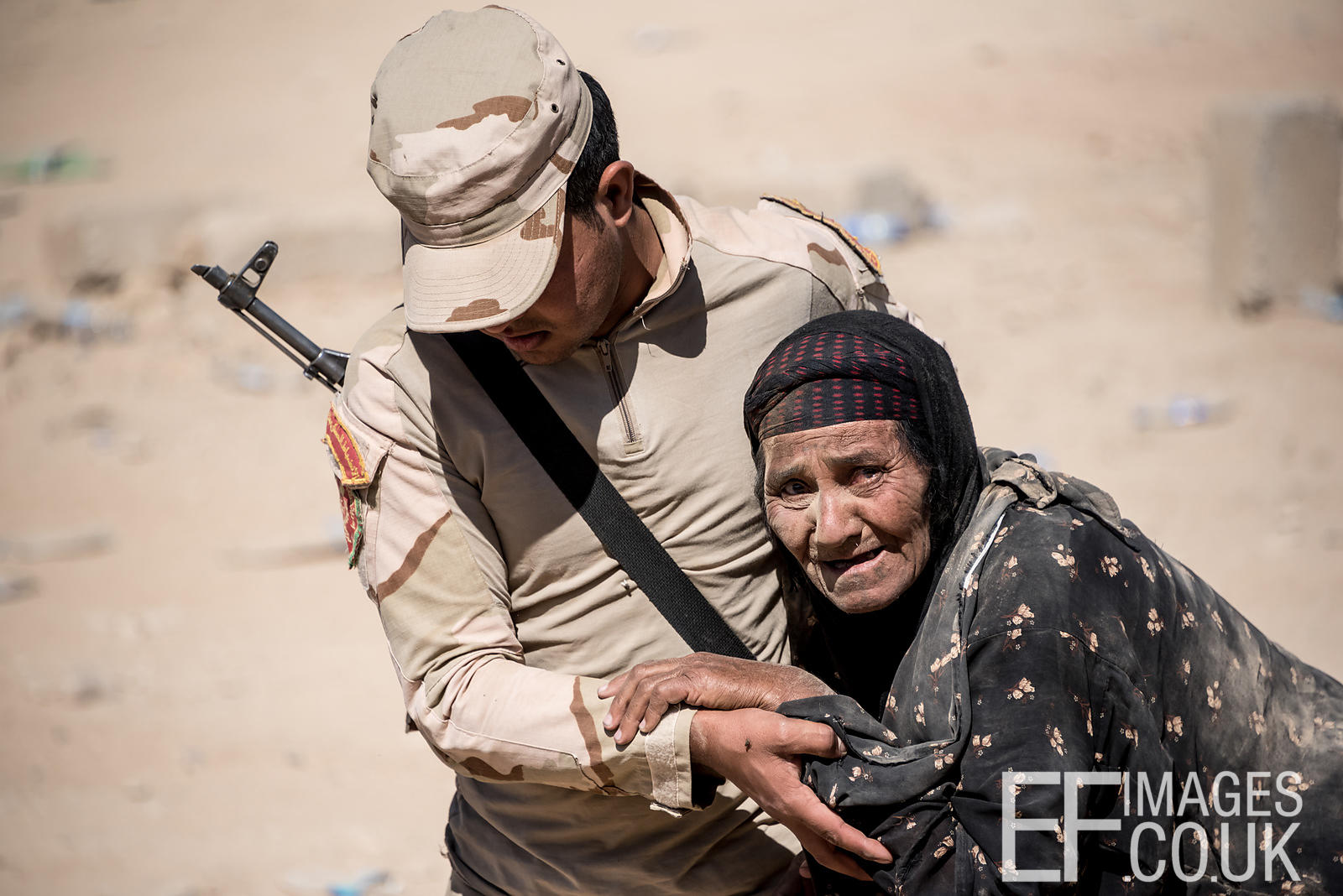 Iraqi Army Soldier helping an old woman to reach a field hospital after she fled her home in Mosul that morning to escape the...