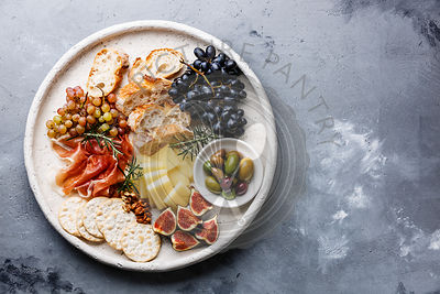 Italian snacks food with Ham, Olive, Cheese, Grapes, Sausage and Bread on concrete background copy space
