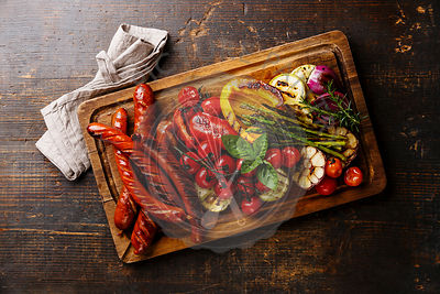 Grilled sausages and vegetables on cutting board on dark wooden background