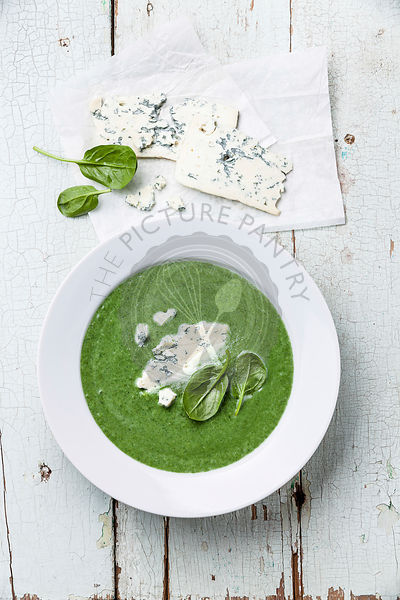 Spinach soup with cheese in white bowl