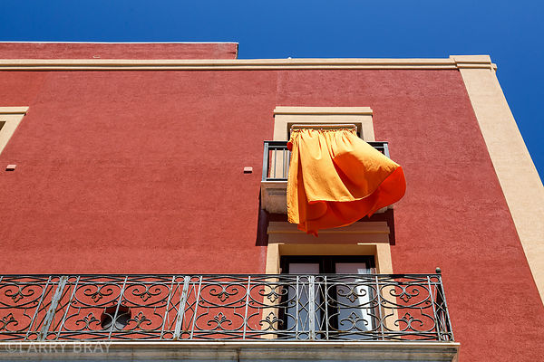 Close up of Terracotta building exterior with orange curtain blowing in the breeze in Trapani, Italy