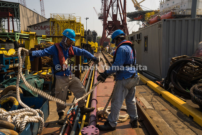 Braving the sun, shipwright workers work hand in hand to tidy up mooring lines in the yard.