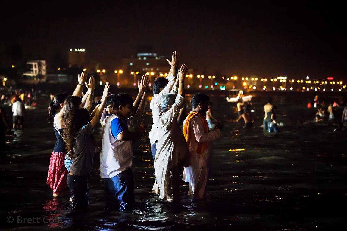 Families pray at night in the Arabian Sea at Chowpatty Beach during the Ganesh Chaturthi festival in Mumbai, India.