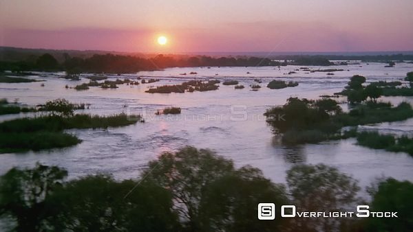 Aerial wide shot flowing river with trees at sunset sunrise and sun reflecting on water Botswana