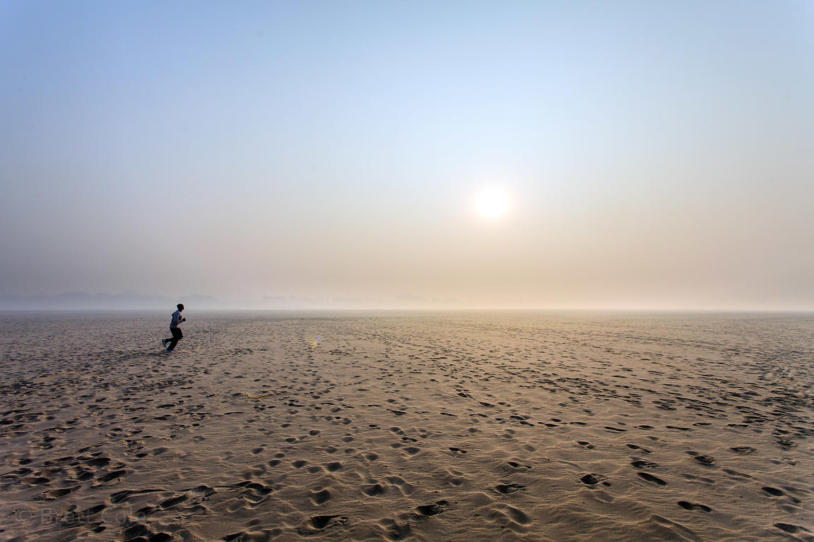 A man jogs on the sandy banks of the Ganges River, Varanasi, India.
