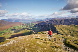 A hiker walking down towards High Snab Bank from the summit of Robinson in the Lake District, England, UK.