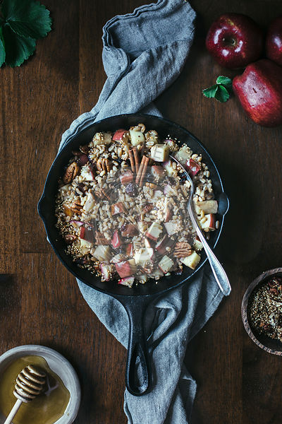 A cast iron skillet filled with warm farro and cinnamon apples