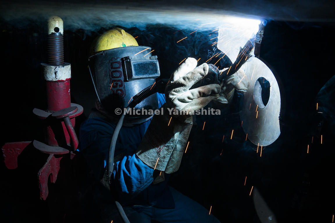 A welder dons protective gear to ensure safety at work.