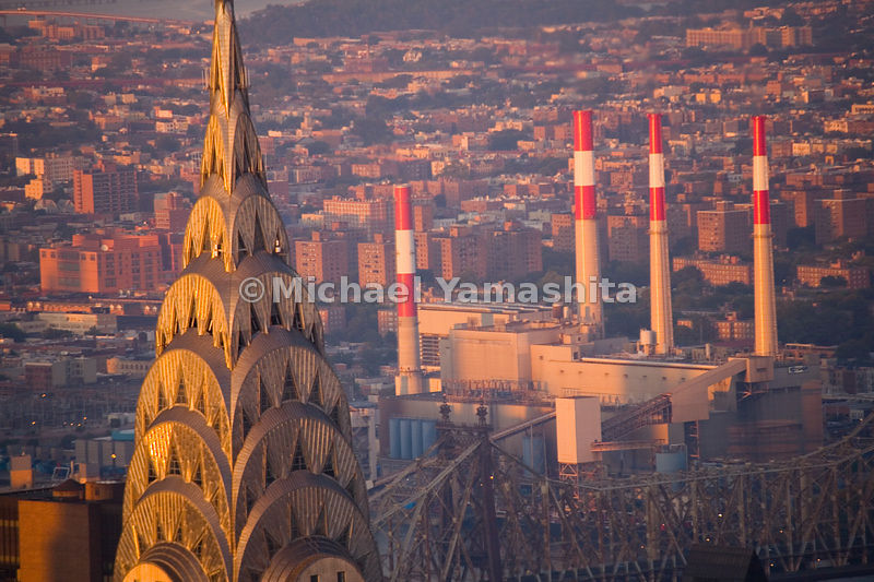 The stainless steel of the Chrysler Building reflects the bright red of the ConEd power plant in the borough of Queens across...