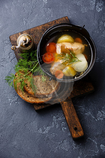 Fish soup with salmon, potato and carrot in black iron pot on dark stone background