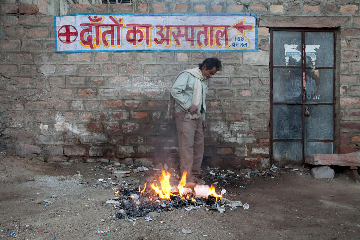In a ritual repeated across India every morning, a man warms himself by a pile of burning garbage, Jodhpur, Rajasthan, India