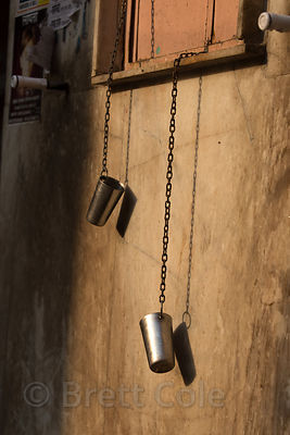 Metal drinking water cups hang from a window, Pushkar, Rajasthan, India