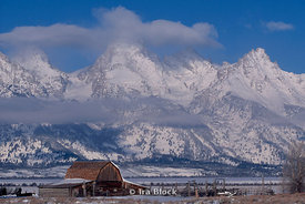 A weathered barn and fences at the foot of the rugged Tetons.