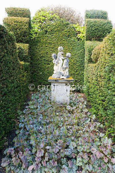 Aged stone statuary surrounded by yew hedges and heuchera. Holker Hall, Grange over Sands, Cumbria, UK