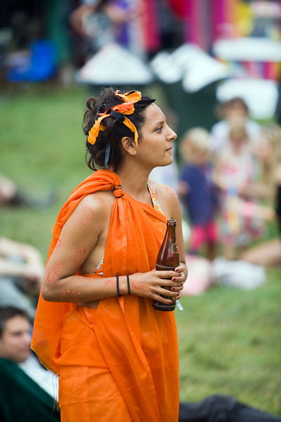 UK - Standon - A woman in a toga costume with a bottle of beer watches and dances to music at the Standon Calling Festival