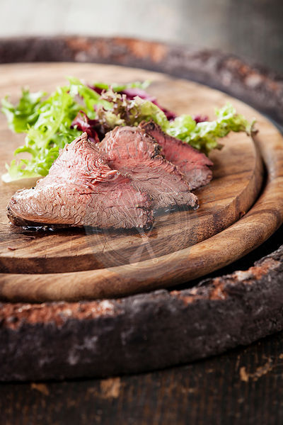 Roast beef on cutting board with lettuce