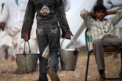 A boy carries buckets of water at the 2010 Pushkar Camel Fair, Rajasthan, India
