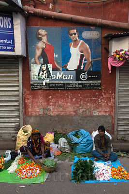 A man sells flowers under macho advertisements on a street in Shyambazar, Kolkata, India.