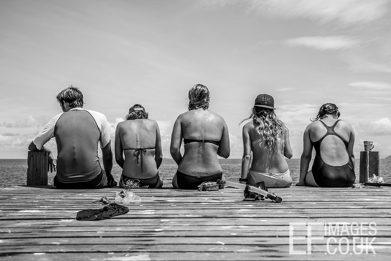 Friends Sitting On A Wooden Jetty
